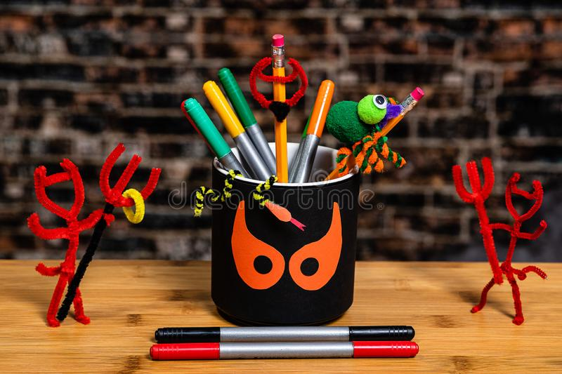 Close up of a pencil cup with spooky halloween eyes surrounded by Pipe Cleaner Devils and other scary objects.  Some Negative. Close up of a pencil cup with royalty free stock photo