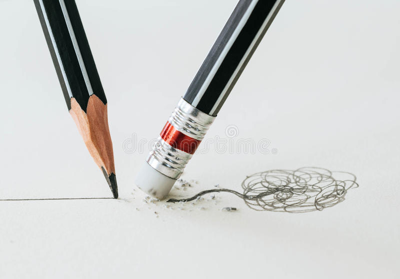 Close up of a pencil eraser removing a crooked line and the close up of a sharpened pencil writing a straight line. royalty free stock photo