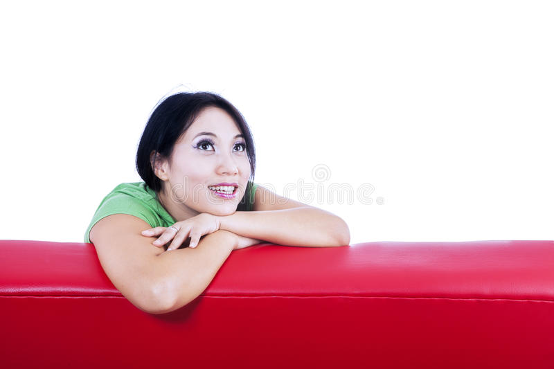 Close-up pensive female on red sofa - isolated