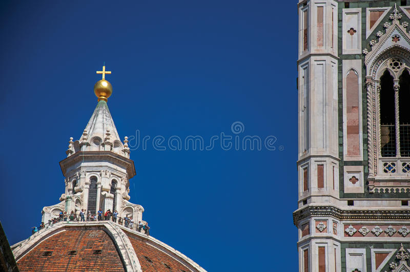 Close-up of people on the dome of the Santa Maria del Fiore Cathedral and Giotto`s Campanile in Florence. stock photos