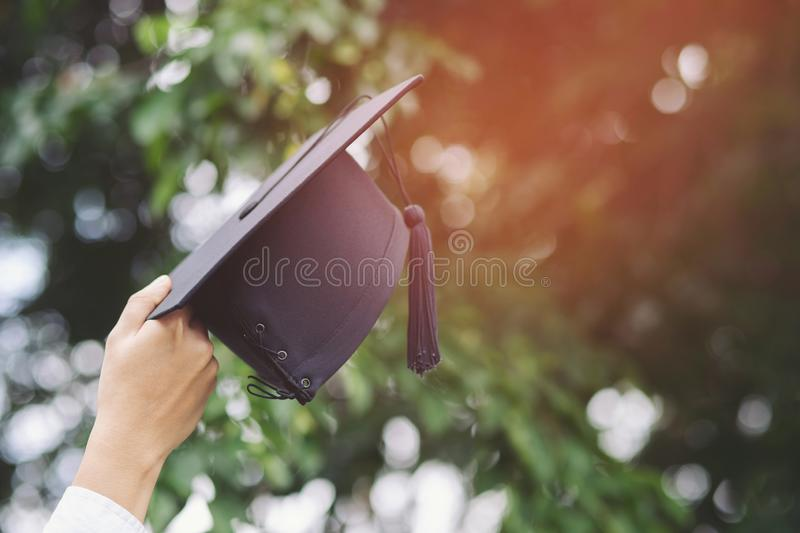 Close up people graduate show hand hold show hat in background outdoor. Shot of graduation cap during Commencement University Degr stock photo