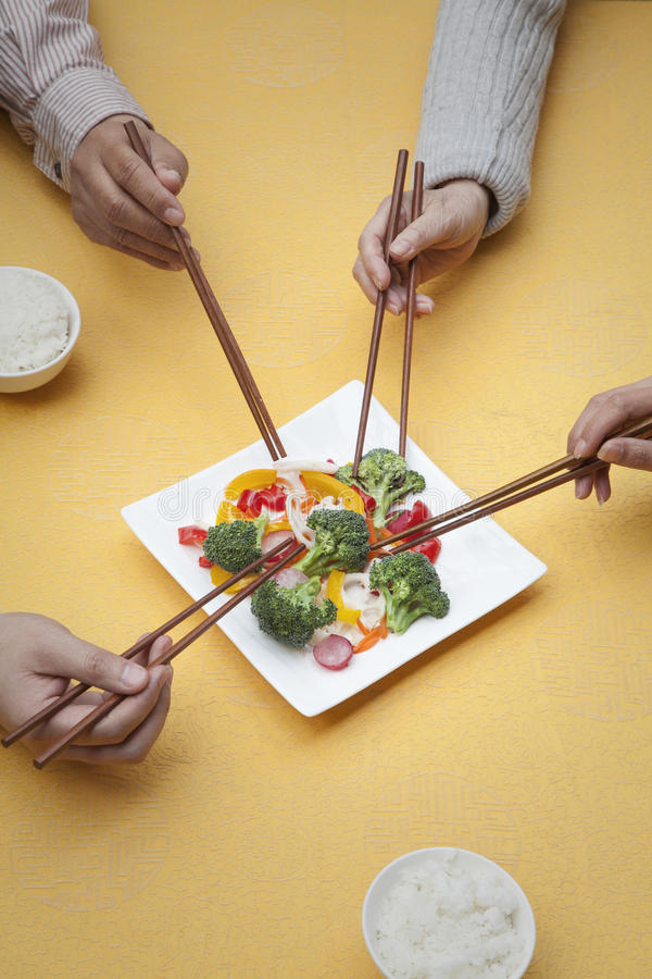 Close up of people holding chopsticks and sharing one dish stock photo