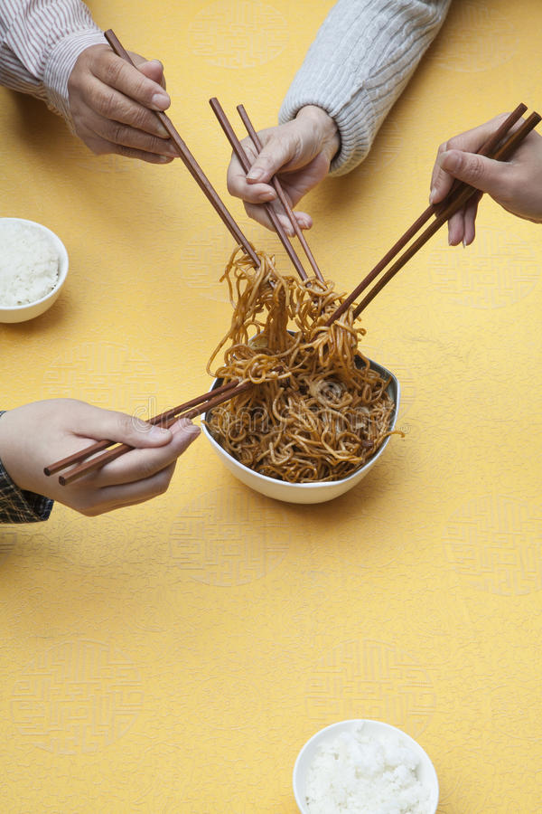 Close up of people holding chopsticks and sharing one dish royalty free stock image