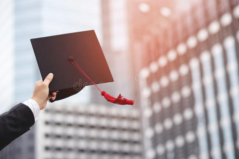 Close up people show hand hold show hat in background School building. Shot of graduation cap during Commencement University Degre royalty free stock images