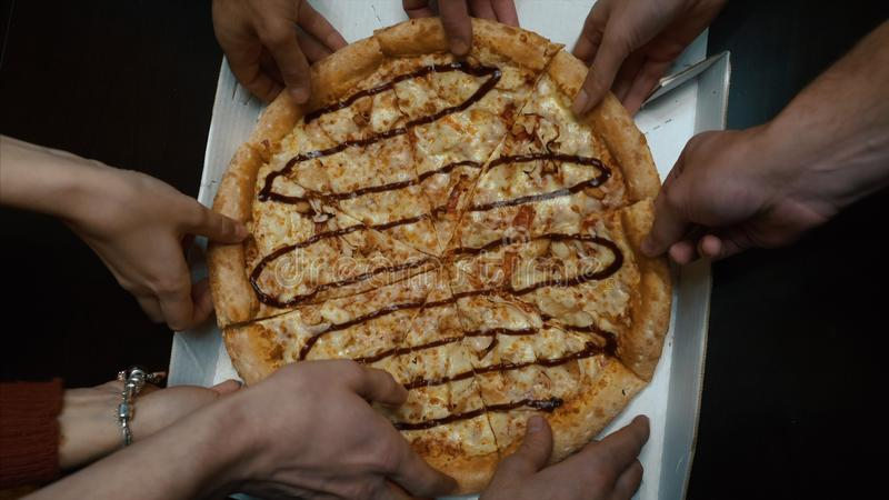 Close up of people taking slices of different pizzas. Group of multi ethnic friends eating Italian pizza take away royalty free stock images