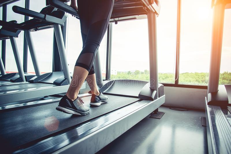 Close up of people who exercising on treadmill. Close-up of woman legs walking by treadmill in sports club. Fitness and Body stock photo
