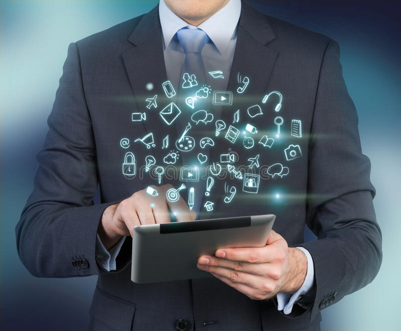 Close-up of a person in a formal suit who holds a tablet with glowing mobile app icons. Dark blue background royalty free illustration
