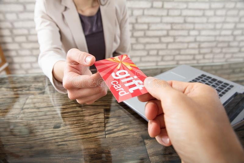Colleague Gives Gift Card To Businesswoman. Close-up Of A Person Giving Gift Card To Businesswoman At Workplace In Office royalty free stock image