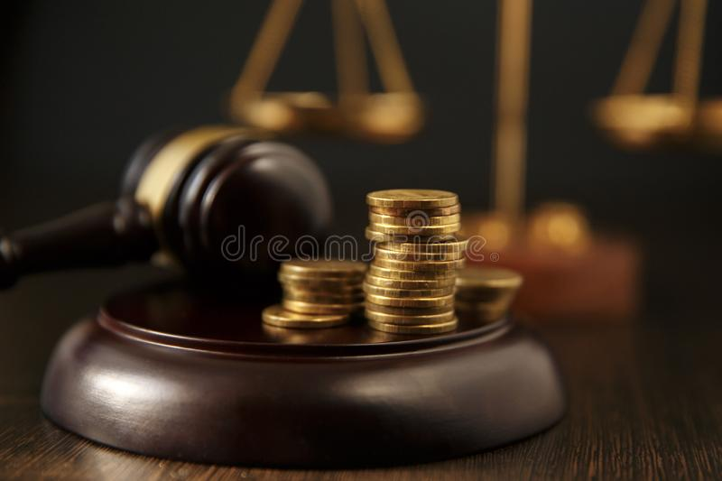 Close-up Of A Person Hand Stacking Coins In Front Of Mallet Over Gray Background stock image
