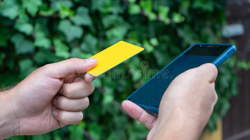 Person paying with credit card in e commerce by touchscreen using phone. Shopping with online banking. Consumer Booking in website. Close up Person paying with royalty free stock photo