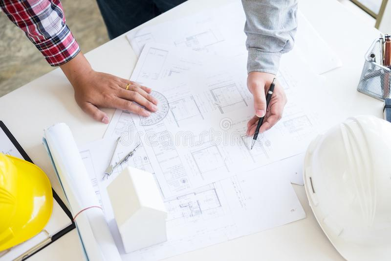 Close-up Of Person`s engineer Hand Drawing Plan On Blue Print wi. Th architect equipment, Architects discussing at the table, team work and work flow stock photo