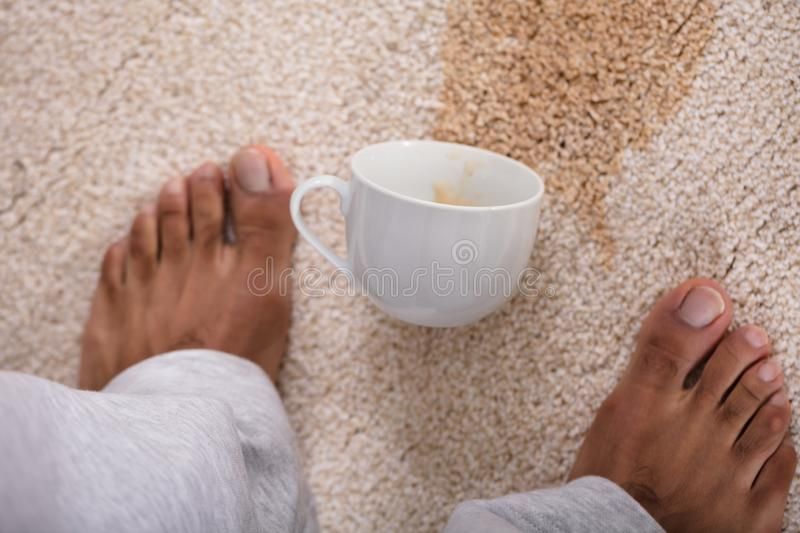 Person`s Feet Standing Near Spilled Coffee. Close-up Of A Person`s Feet Standing Near Spilled Coffee On Carpet stock photos