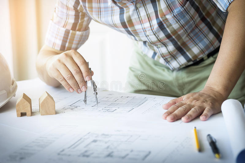 Close-up Of Person& x27;s Hand Drawing Plan On Blue Print with archit royalty free stock photography