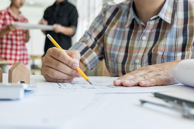 Close-up Of Person& x27;s Hand Drawing Plan On Blue Print with archit royalty free stock photo