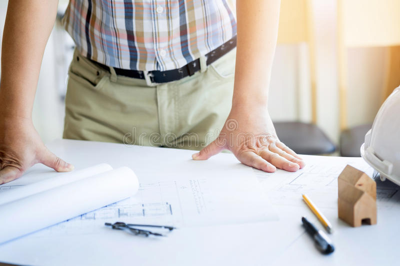 Close-up Of Person& x27;s Hand Drawing Plan On Blue Print with archit stock photography