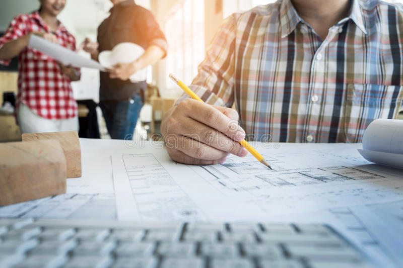 Close-up Of Person& x27;s Hand Drawing Plan On Blue Print with archit stock photo
