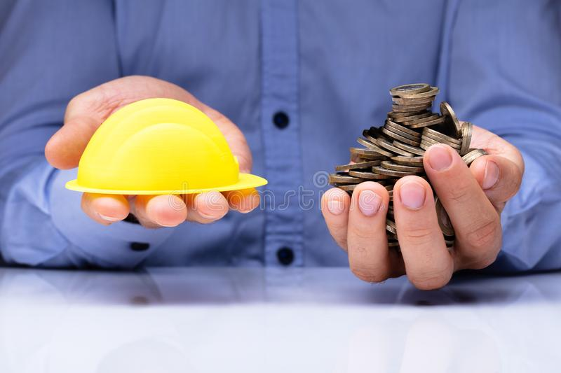 Person Holding Hardhat And Golden Coins royalty free stock photos