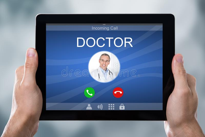 Person`s Hand Holding Tablet With Doctor`s Incoming Call stock photos