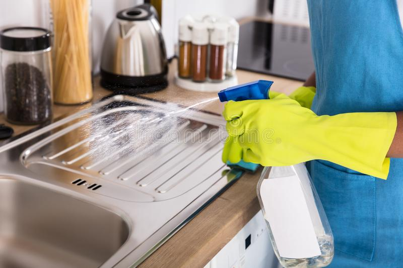 Person Using Spray Bottle For Cleaning Kitchen Sink royalty free stock photography
