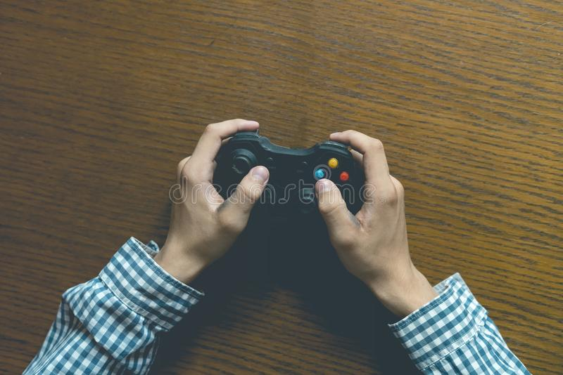 Close up person`s hands playng video game isolated on wooden table concept stock photo