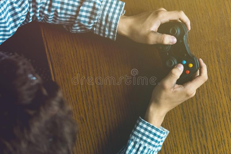 Close up person`s hands playng video game on wooden table concept royalty free stock photos