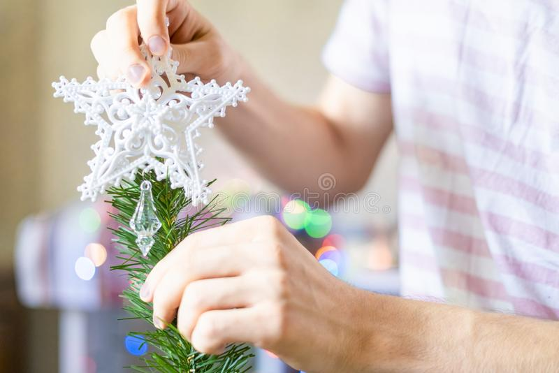 Close up person`s hands putting white decoration star on top of christmass tree f royalty free stock image