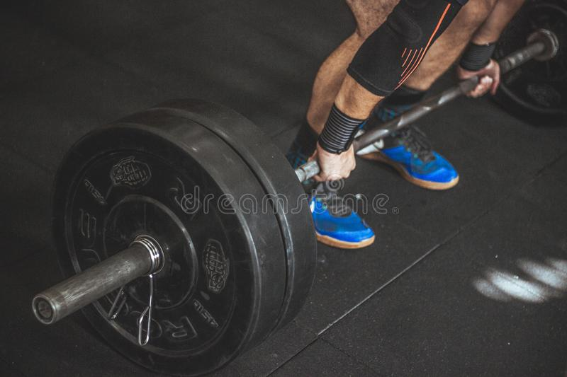 Close-up of a Person's Lower Body Holding Barbell stock photo
