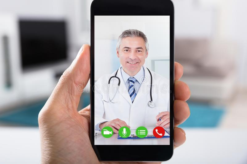 Person Video Conferencing With Doctor On Smartphone. Close-up Of A Person Video Conferencing With Happy Male Doctor On Smartphone stock photos
