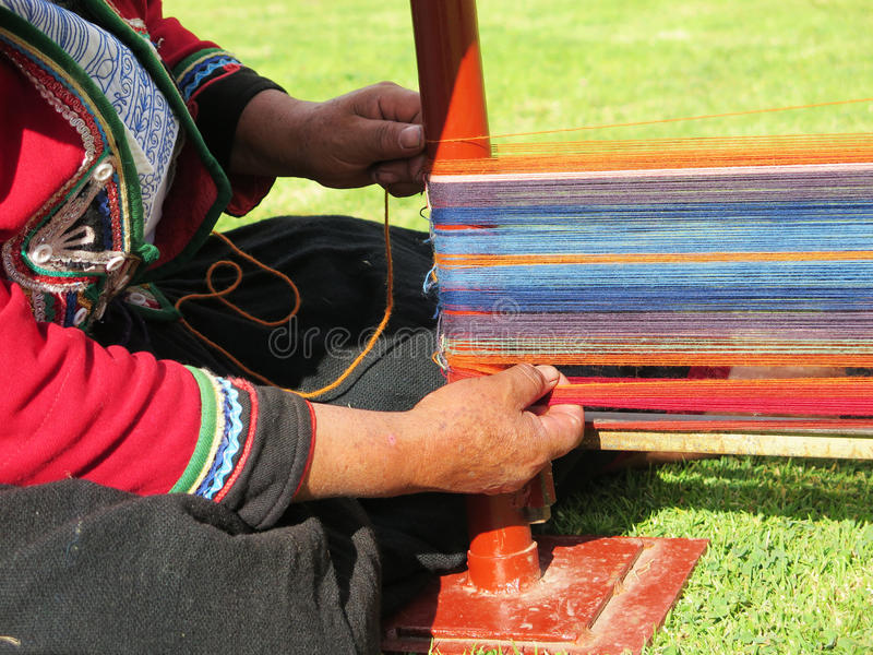 Close up of Peruvian lady in authentic dress spinning yarn by ha. Nd. Peru royalty free stock photo
