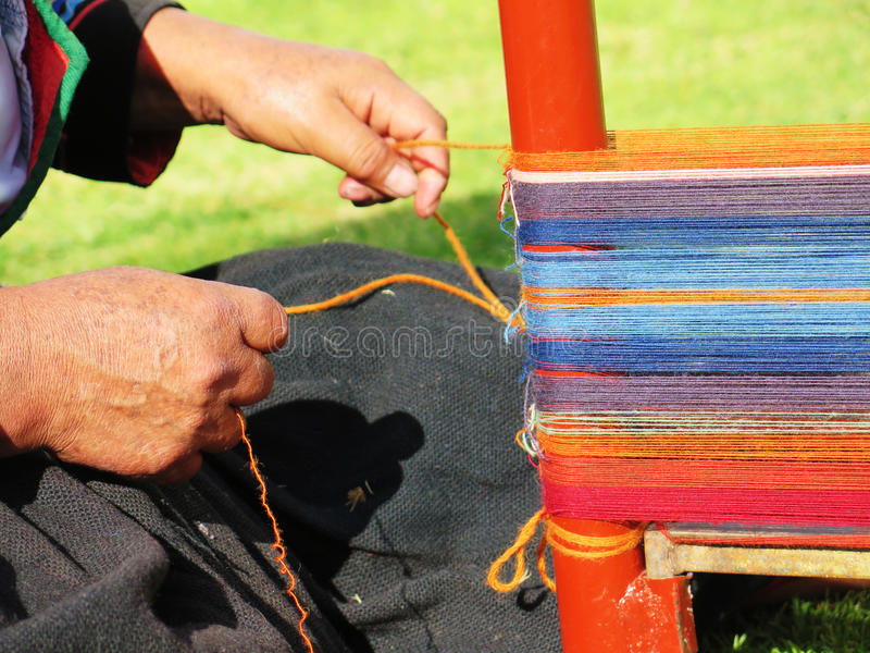 Close up of Peruvian lady in authentic dress spinning yarn by ha. Nd. Peru royalty free stock photos