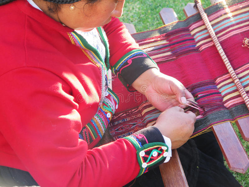 Close up of Peruvian lady in authentic dress spinning yarn by ha. Nd. Peru stock photography