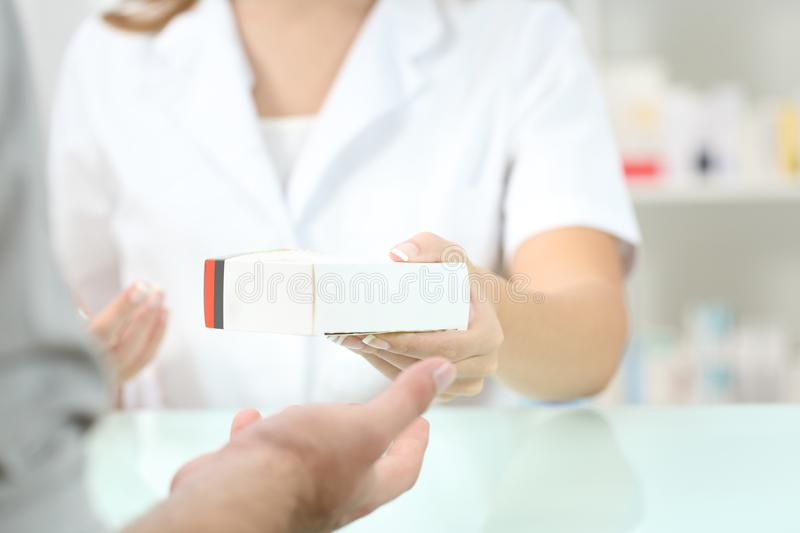 Pharmacist giving a medicament to a customer. Close up of a pharmacist hand giving a medicament to a customer royalty free stock photo