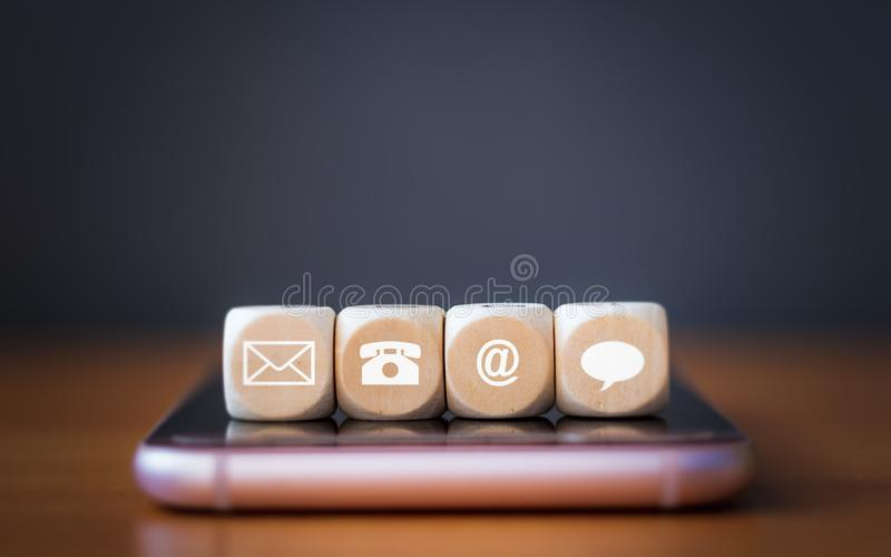 Close-up of a phone, email, chat and post icons wooden dice arranging in a row on mobile phone royalty free stock photography