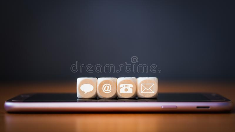 Close-up of a phone, email, chat and post icons wooden dice arranging in a row on mobile phone stock images