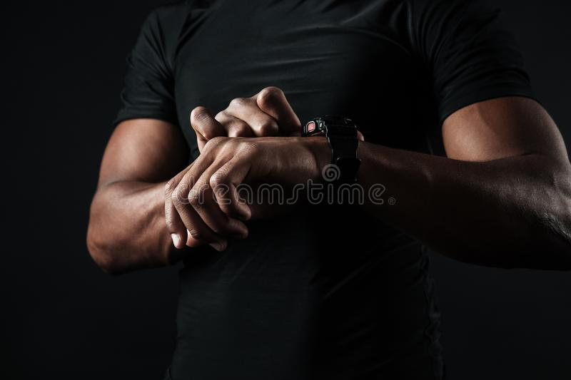 Close-up photo of african man in black t-shirt check out time at royalty free stock photo
