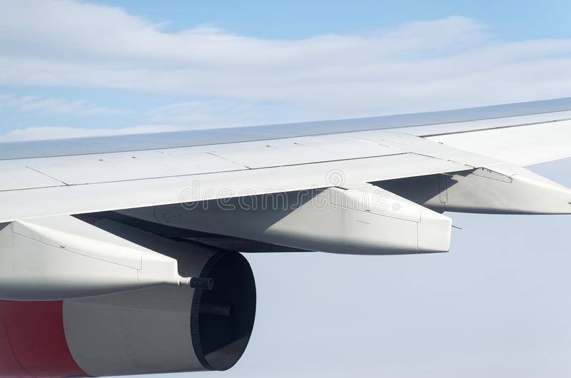 Airplane wing and turbine on a blue cloudy sky stock photo