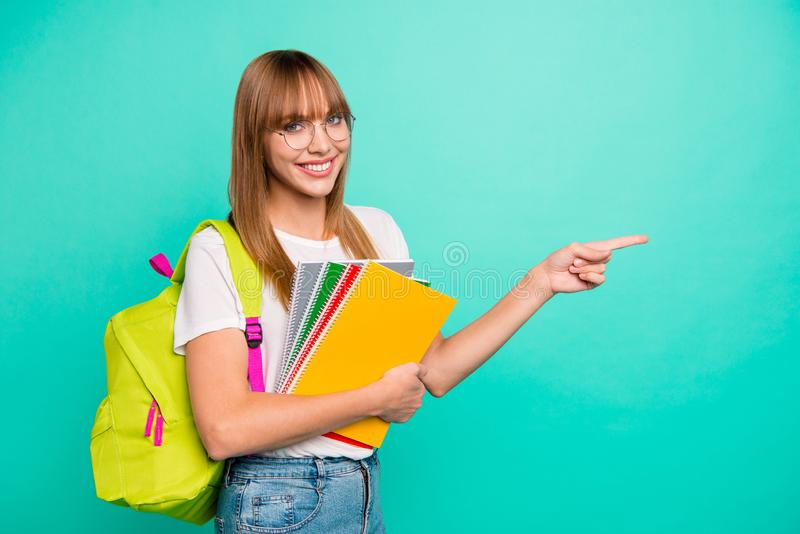 Close up photo amazing beautiful she her lady cheer arms hands school colored notebooks directing empty space last year. Studying science wear specs casual stock photos