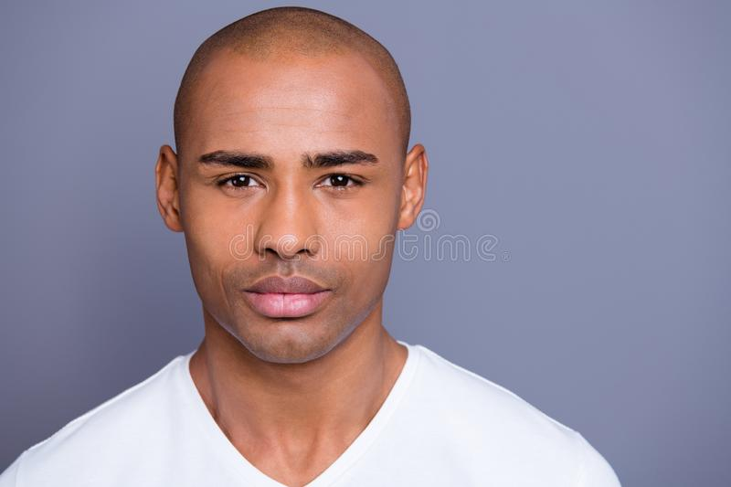 Close up photo amazing dark skin he him his man looking straight on camera kind sincere eyes shiny shaved face wearing. White t-shirt outfit clothes isolated on stock photography