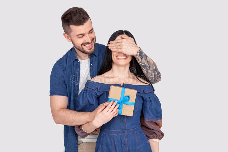 Close up photo amazing lady guy hide eyes guess who game prepared romance surprise hold big giftbox wear casual jeans denim shirts. Outfit clothes isolated grey stock photos