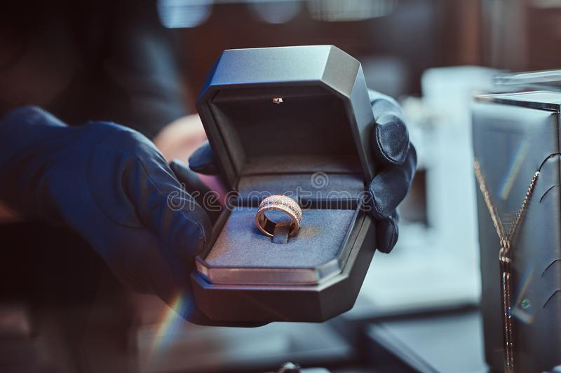 Close-up photo of assistant`s hands who holds the box with the exclusive gold ring in a jewelry store stock image