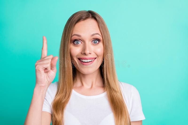 Close up photo of astonished funny person pointing index finger up wearing white t-shirt isolated over teal turquoise. Close up photo of astonished, funny person stock photography