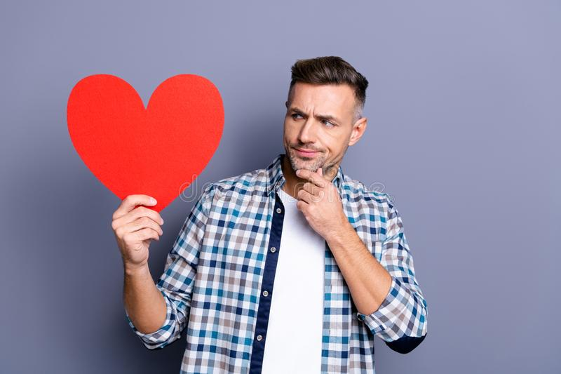 Close up photo attractive he him his guy arms hands large red paper heart not sure agree celebration valentine day hate royalty free stock images