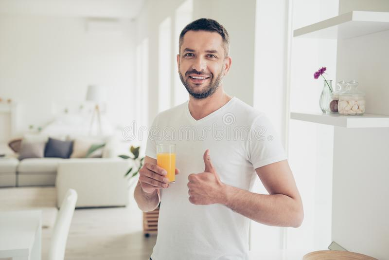 Close up photo attractive he him his homey guy arm hand orange juice glass energy refreshment thumb up symbol advising. Close up photo attractive he him his royalty free stock photos