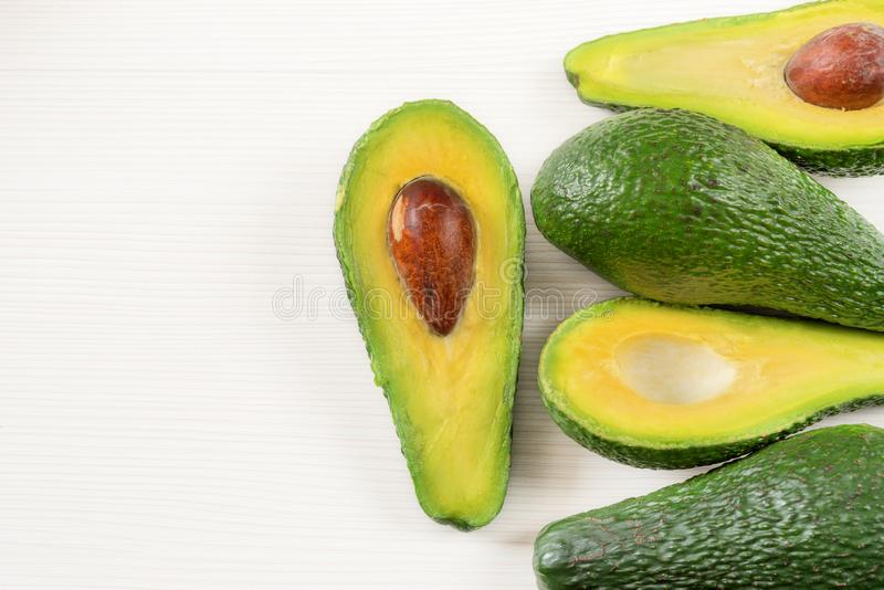 Close-up photo of avocados cut to half, brown seeds visible, with more avocados on white wooden background. stock photography