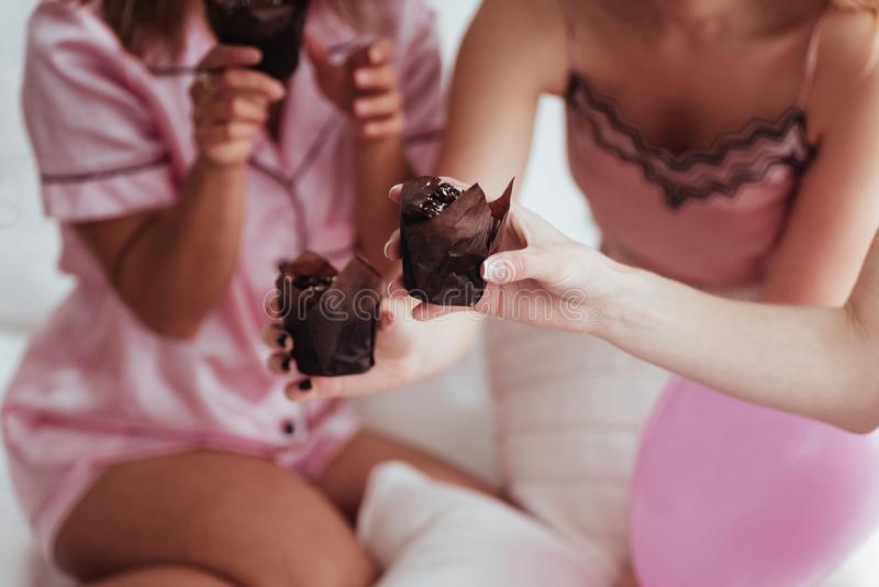 Close up photo. Bachelorette party in the bedroom. Delicious looking chocolate cookies at the girlish day. Four women in royalty free stock photos