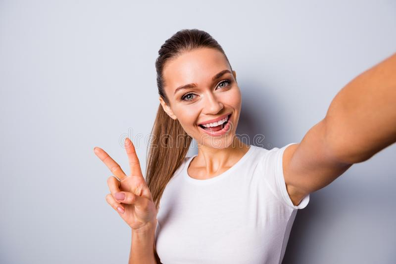 Close up photo beautiful amazing funky she her lady perfect appearance make take selfies show v-sign say hi instagram. Followers weekend mood wear casual white stock photography
