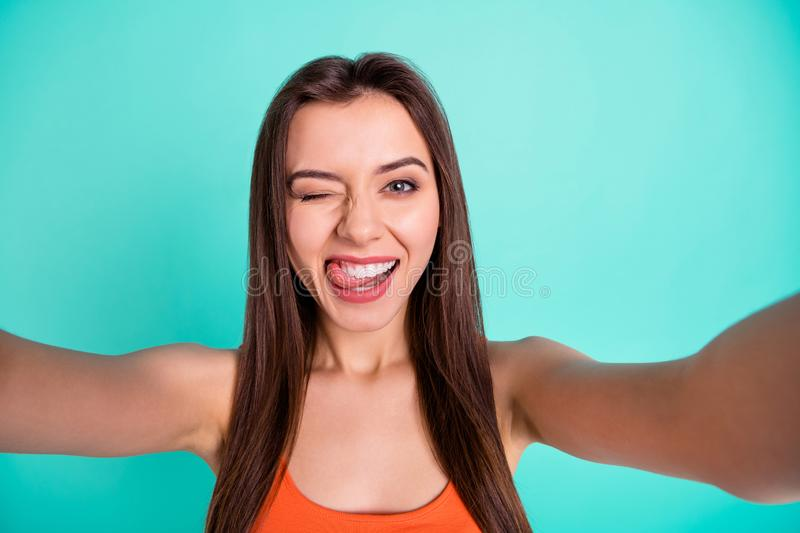 Close up photo beautiful amazing her she lady make take selfies tell speak say skype tongue out mouth blink one eye. Flirty wear casual orange tank-top  bright royalty free stock photography