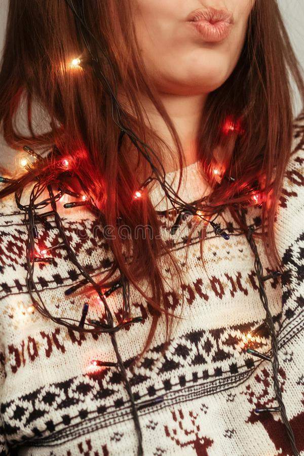 Close-up photo of beautiful brunette woman in white stylish sweater with reindeers tangled with colorful, red and. Yellow, christmas lights, greeting card royalty free stock photos