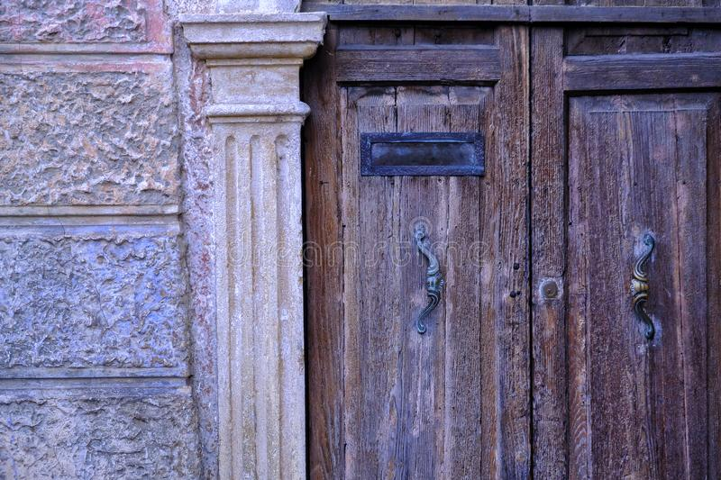 Ancient wooden door and mailbox. Close up photo of a beautiful example of ancient architecture. You may see old stone house and quite detailed almost colorless stock images
