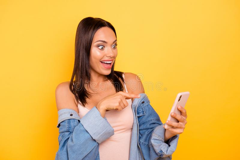 Close up photo beautiful she her lady telephone hands arms funny funky direct indicate finger screen devise amazed wear. Casual pastel tank-top jeans denim royalty free stock photo